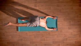 Übersteigen Sie hinunter Schuss, muskulöser Sportler tut Yoga auf der blauen Matte mit großer Konzentration und seine Hände und B stock footage
