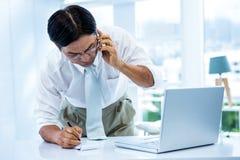 Überwältigter asiatischer Geschäftsmann, der das Telefon und das Schreiben beantwortet Lizenzfreie Stockfotos