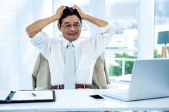 Überwältigter asiatischer Geschäftsmann, der verrückt geht Lizenzfreie Stockfotografie