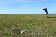 Überwältigter Mann, der in Feld weg von Laptop läuft Stockfotografie