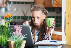 Überwältigter Student in der Küche mit Laptop Stockfotos