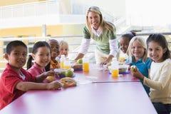 Überwachende Kinder der Kindergärtnerin stockfoto