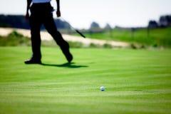 Überwachende Kugel des Golfspielers auf Grün Lizenzfreies Stockfoto