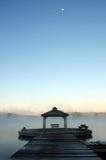 Überwachende Sonne der Frau, als Nebel zu steigen steigt vor See Stockfoto