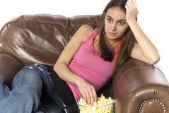 Überwachender Popcorn essender und entspannender Fernsehapparat Stockfotos