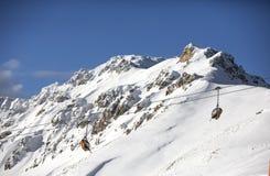 Überwachender Schnee der Frau deckte Berge ab Alpen, Winterlandschaft Makro des grünen Grases Sesselbahn Bellamonte, Lusia, Valbo Stockbild