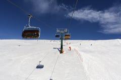 Überwachender Schnee der Frau deckte Berge ab Alpen, Winterlandschaft Makro des grünen Grases Sesselbahn Bellamonte, Lusia, Valbo Lizenzfreies Stockfoto