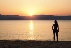 Überwachender Sonnenuntergang der jungen Frau Stockbilder