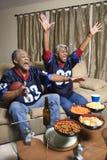 Überwachender Sport der von mittlerem Alter African-Americanpaare auf Fernsehapparat. stockfoto