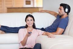 Überwachendes Fernsehen der Frau mit ihrem Ehemann stockfotos