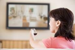 Überwachendes Fernsehen der Frau unter Verwendung Fernsteuerungs Stockfoto