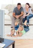 Überwachendes Fernsehen der glücklichen Familie zusammen Stockfotos