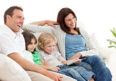 Überwachendes Fernsehen der glücklichen Familie zusammen lizenzfreie stockfotografie
