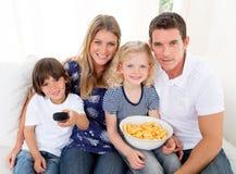 Überwachendes Fernsehen der liebevollen Familie, das auf Sofa sitzt stockfotografie