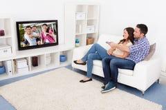 Überwachendes Fernsehen der Paare Stockbilder