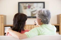 Überwachendes Fernsehen der Paare unter Verwendung Fernsteuerungs Stockfotos