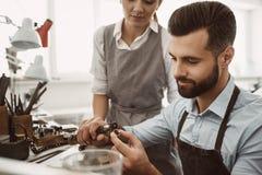Überwachung des Fortschritts Nahaufnahmeporträt des jungen männlichen Juweliers, der einen Ring poliert, während weiblicher Meist lizenzfreies stockbild