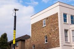 Überwachungskamera auf einem Pfosten, der ein Haus überwacht Stockbild