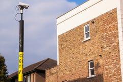Überwachungskamera auf einem Pfosten, der ein Haus überwacht Stockfotos