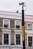 Überwachungskamera auf einem Pfosten mit Wohnungen im Hintergrund Lizenzfreies Stockbild