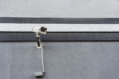Überwachungskamera auf Schwarzweiss-Wand in der Straße Stockfotos