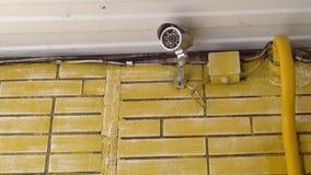 Überwachungskamera, die über dem Eingang eines Hauses hängt stock video