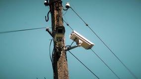 Überwachungskamera, die an einem Pfosten auf Hintergrund des blauen Himmels hängt stock video