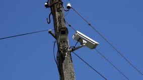 Überwachungskamera, die an einem Pfosten auf Hintergrund des blauen Himmels hängt stock footage