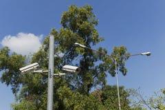 Überwachungskamera und Laternenpfahl im Park Stockbilder