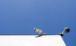 Überwachungskameras auf Wand draußen über blauem Himmel lizenzfreies stockfoto
