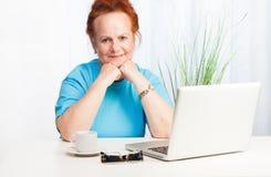 Überzeugte ältere Frau mit Laptop Stockfoto