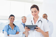 Überzeugte Ärztin, die Tablette mit ihrem Team hinten hält Lizenzfreie Stockbilder