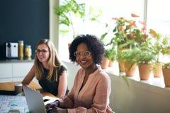 Überzeugte afrikanische Geschäftsfrau, die mit einem Kollegen in einem O arbeitet stockbilder