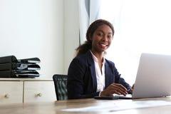 Überzeugte afrikanische Geschäftsfrau, die am Schreibtisch mit Laptop sitzt stockbild
