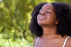 Überzeugte Afroamerikanerfrau draußen in einem Garten Lizenzfreie Stockfotografie