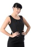 Überzeugte anspruchsvolle positive glückliche Frau, die im schwarzen Kleid lächelt Lizenzfreies Stockbild
