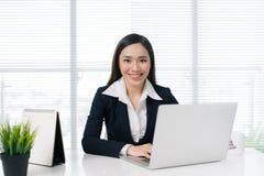 Überzeugte asiatische Geschäftsfrau, die durch Schreibtisch mit Laptop herein weg sitzt Stockbilder
