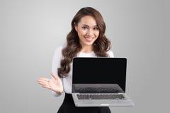 Überzeugte asiatische Geschäftsfrau, die Laptopschirm zeigt Stockfoto
