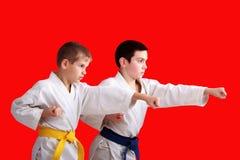 Überzeugte Athleten bilden Schlagarme auf dem roten Hintergrund aus lizenzfreies stockbild