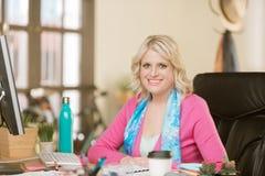 Überzeugte Berufsfrau, die ein rosa Strickjacke Lächeln trägt stockfoto