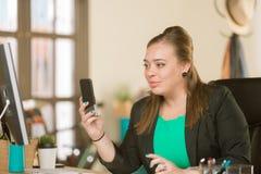 Überzeugte Berufsfrau, die ihr Telefon verwendet stockfotos