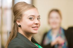 Überzeugte Berufsfrau, die mit Klammern lächelt stockfotos