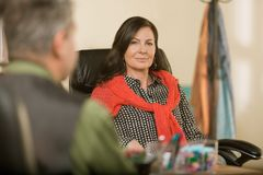 Überzeugte Berufsfrau, die am Schreibtisch sitzt stockbilder