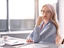 Überzeugte blonde Frau, die im Büro arbeitet Stockfoto