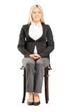 Überzeugte blonde Geschäftsfrau in der Klage, die auf einem Stuhl sitzt Lizenzfreies Stockbild