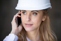 Überzeugte blonde Geschäftsfrau im Schutzhelm sprechend auf Smartphone und weg schauend Lizenzfreies Stockfoto
