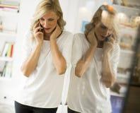 Überzeugte blonde Geschäftsfraustellung und mit Telefon in einem O Lizenzfreie Stockbilder