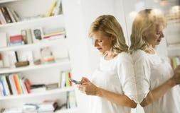 Überzeugte blonde Geschäftsfraustellung und mit Telefon in einem O Stockbilder