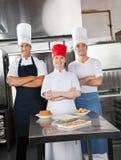 Überzeugte Chefs mit süßen Tellern auf Küche Stockfotos