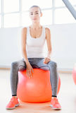 Überzeugte dünne Frau, die auf einem Eignungsball sitzt Stockfoto